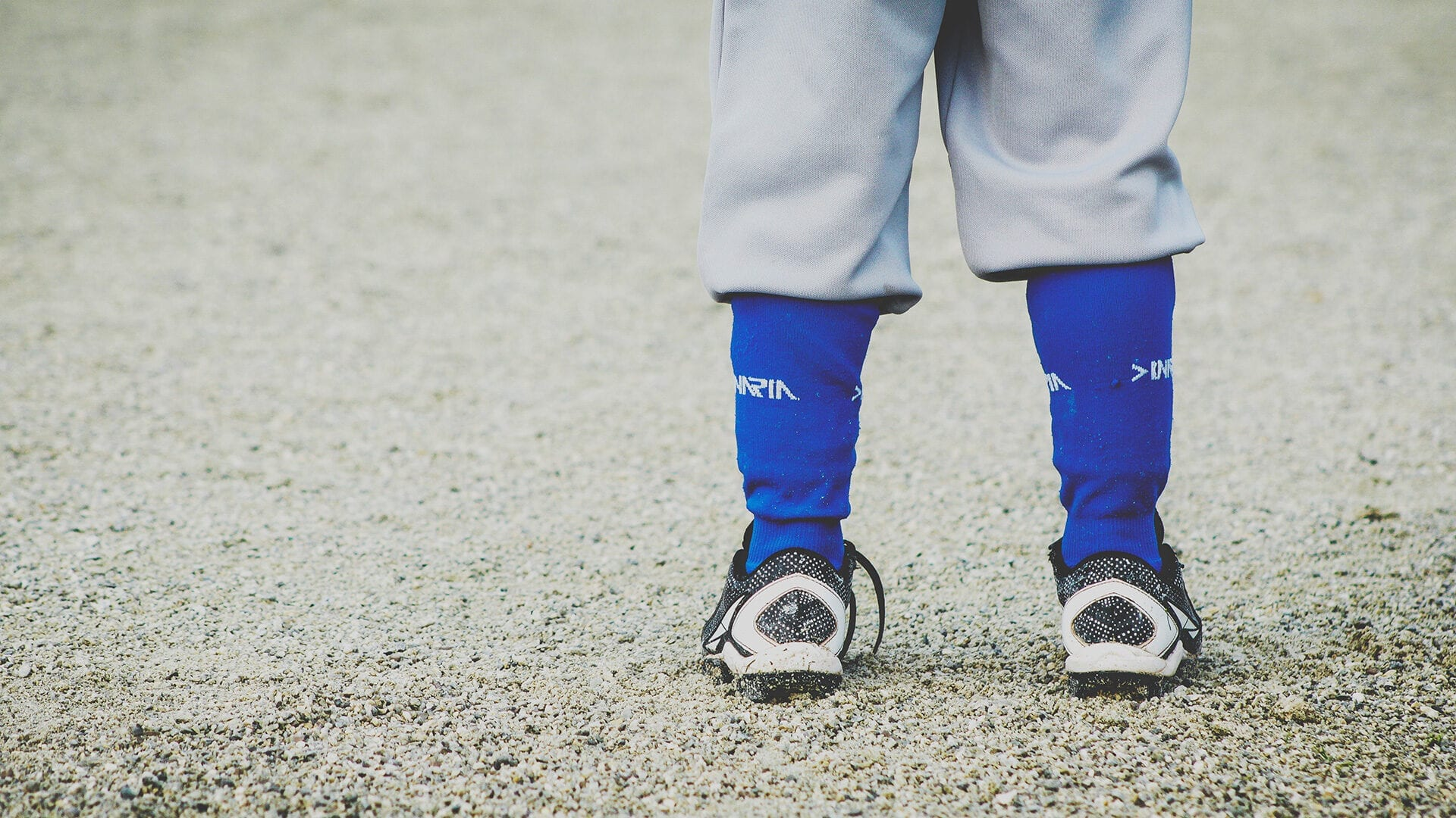 A child's ankles dressed in sports socks and cleats