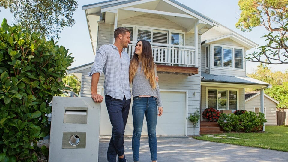 Happy couple standing outside of a house