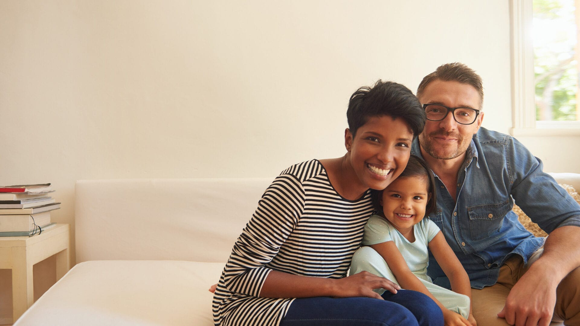 A smiling family of 3 sitting in living room