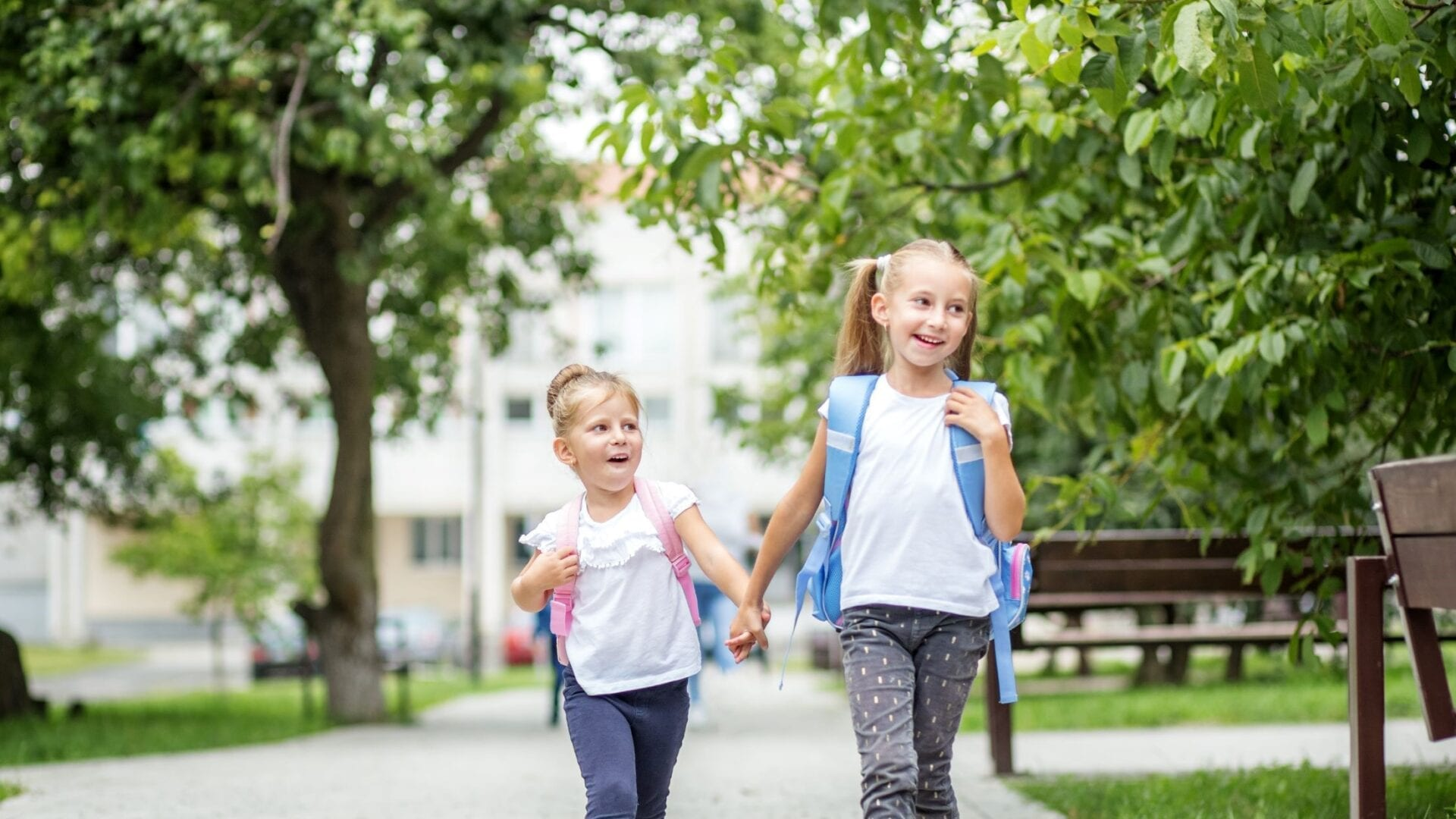 Two girls holding hands with backpacks on
