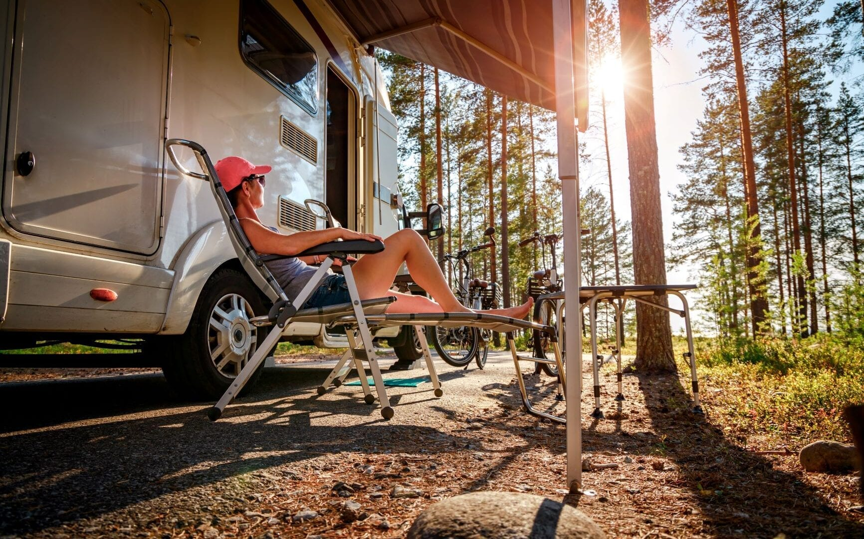 Woman relaxing outside of her RV at sunrise