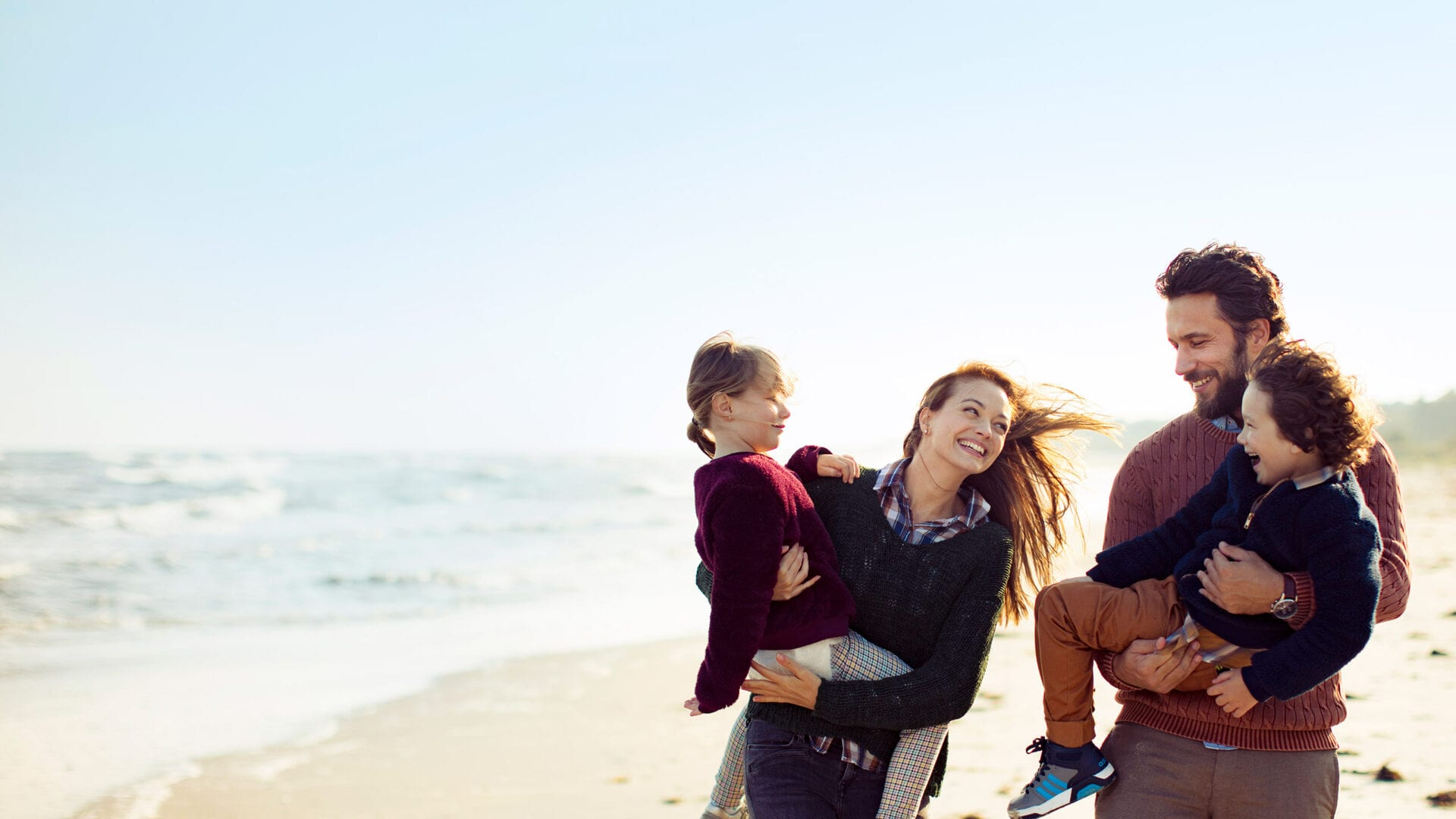 Family of four walking along beach in cool weather
